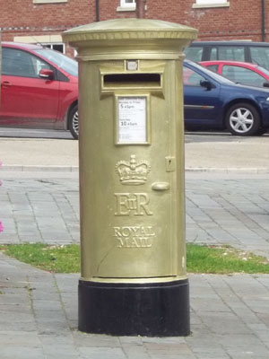 A gold-painted Royal Mail postbox