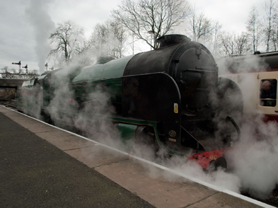 A steam train standing at a platform