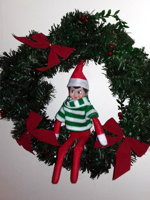 An Elf sitting on a Christmas wreath