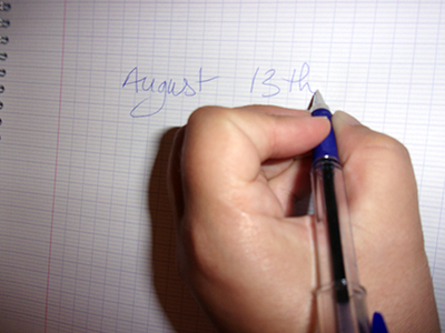 A left-handed writer noting Left Handers Day