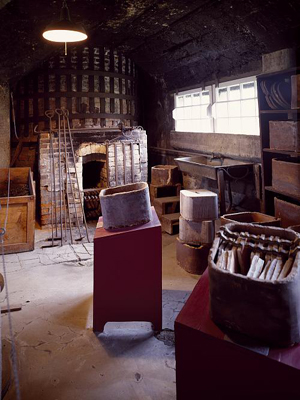 A photograph of an old pottery workshop, showing a saggar on a bench.
