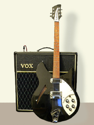 Photograph of a Rickenbacker Guitar in front of an amp.