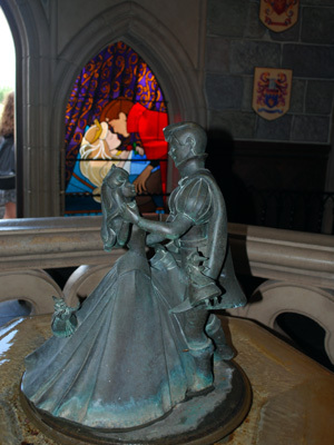 A 3D model of Aurora and Prince Phillip in front of a 2D stained-glass window portrait of Aurora and Prince Phillip in Sleeping Beauty's Castle