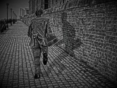A man and his shadow running along a cobbled street