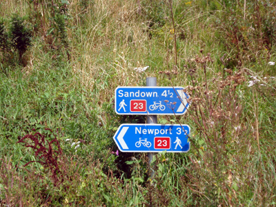 Signs showing how far Sandown and Newport are along National Cycle Route 23