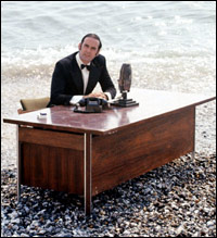 John Cleese, sat at a desk on the shore.