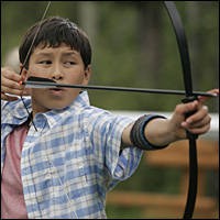 Yudii Mercredi fires an arrow in CBBC's 'Shoebox Zoo'.