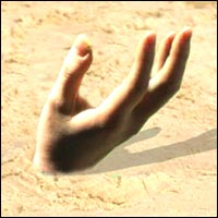 a hand buried in golden sands.
