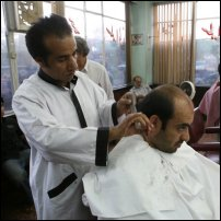 A barber cuts a customer's hair in Kabul.