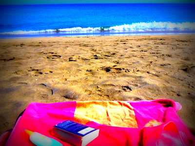 A photo of a beach towel on a sandy beach with blue sea in the background