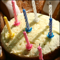 A birthday cake with coloured candles on it.