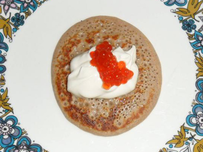 Blini (Russian pancake) with red caviar and sour cream.