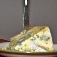 A piece of blue cheese with a knife stuck in it.