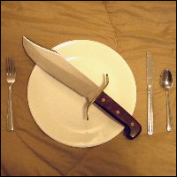 A bowie knife in the middle of a white plate.