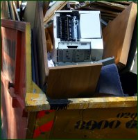 A broken computer languishes in a skip.