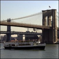 A ferry passing under the Brooklyn Bridge.