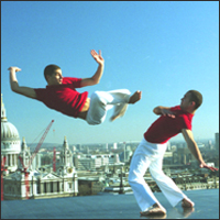 Dressed in red and white, two performers demonstrate various Capoeira moves on a rooftop against a dramatic London backdrop.