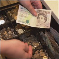 A cashier holds a five-pound note prior to inserting it into a till.