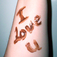 The words 'I love u' painted in chocolate on a bare arm.