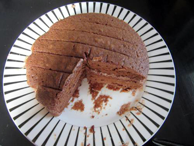 A chocolate sandwich cake with a large slice removed
