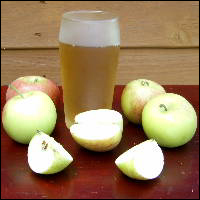 A glass of cider surrounded by apples.