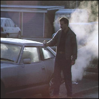 A man de-iceing his car on a cold, frosty morning.