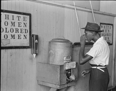 African American man drinking from a water cooler marked 'Colored' in 1939. US Farm Security Administration photo.