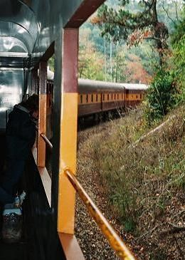 A train driving along a mountain edge.