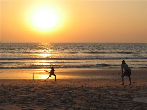 Two people in silhouette playing cricket on a beach at sunset