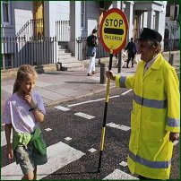 A young girl crossing the road with the help of a Lollipop Lady.