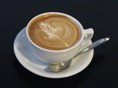 A cup of coffee with saucer and spoon.