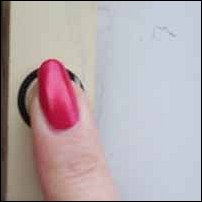 A finger rings a doorbell.