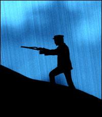 A man climbs a hill while dowsing in the rain.