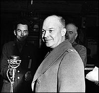 Dwight D Eisenhower addresses a group of assembled journalists.