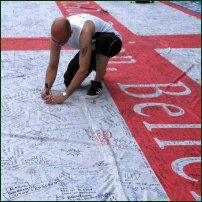 England fan signs a giant St George's flag in front of Cologne cathedral during Fifa World Cup 2006.