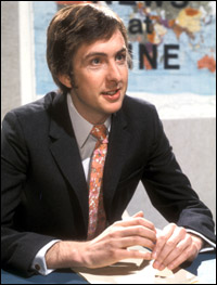 Eric Idle, sitting at a news desk.