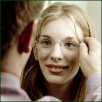 An optician puts glasses on a girl.
