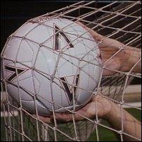 Hands retrieving a football from a net.