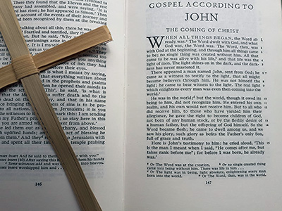 A cross in front of a Bible open at the Gospel according to Saint John