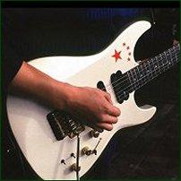 A budding guitarist tries to play a chord.
