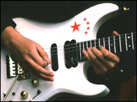 A pair of hands making sweet music with a guitar