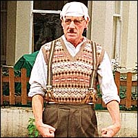 Michael Palin, former Monty Python star, recreating the look of the Gumby by wearing a knotted handkerchief on his head, a woollen tank-top and a stupid facial expression.