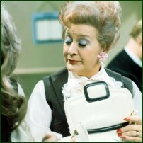 The actress Mollie Sugden, aka Mrs Slocombe, searches in her handbag.