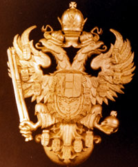 The seal of the Hapsburg family, incorporating a shield, two eagles, and an orb and sceptre, all underneath a crown.