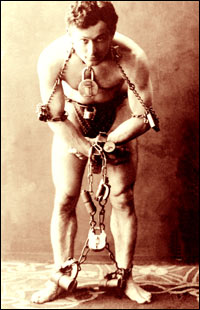 A man stands shackled in chains - don't worry, he'll be free in a minute.