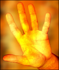 A hand illuminated by flames.