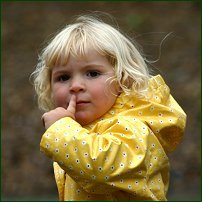 A small girl raises her index finger to her lips.