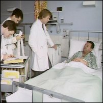 Doctors surround a patient's hospital bed.