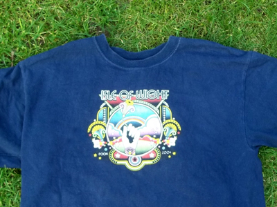 A T-shirt with the Isle of Wight Festival logo lying on the the ground.