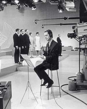 John Barry conducting a small orchestra in a TV studio from 1964
